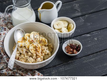 Oatmeal With Banana, Caramel Sauce And Pecan Nuts In A White Bowl On A Dark Wooden Surface, A Delici