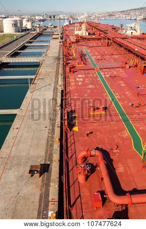 Crude oil tanker ship is moored to a berth in sea port.