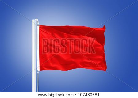 Red flag flying in a stiff breeze against clear blue sky.