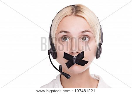 Sexy Young Blond Woman In A Headset Looks Up And Can Not Speak, Because She Put A Plaster On His Mou