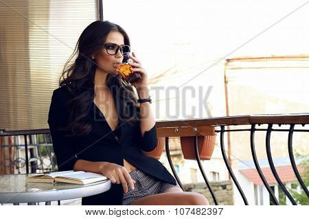 Woman Wearing Black Jacket,watch And  Glasses, Sitting At Cafe And Drinking Tea