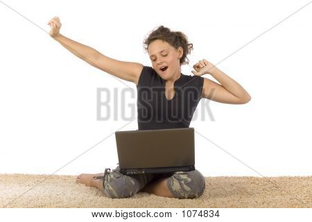 Female Teenager Yawning On The Carpet With Laptop