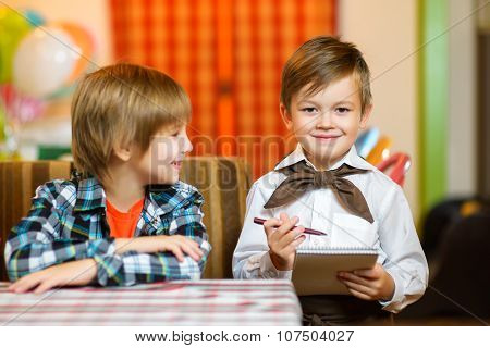 little boy waiter accepts the order in a cafe or restaurant. poster