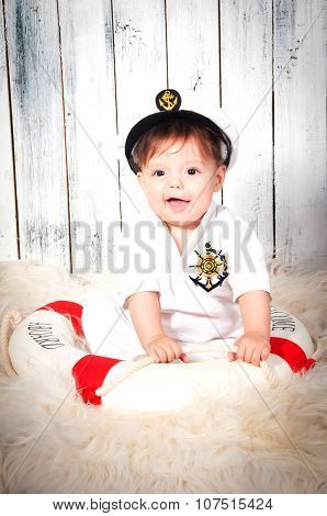 Funny Smiling Little Boy Dressed As A Sea Captain In Naval Cap. Marine Decor, Lifebelt.