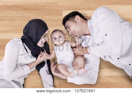 Young Parents And Their Son Lying On The Floor