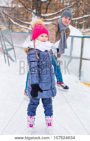 Adorable little girl and happy father on skating rink outdoors