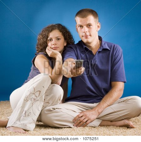 Young Couple On Carpet With Remote Control