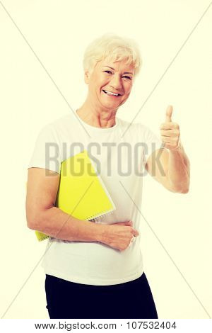 An old woman holding workbook and showing OK