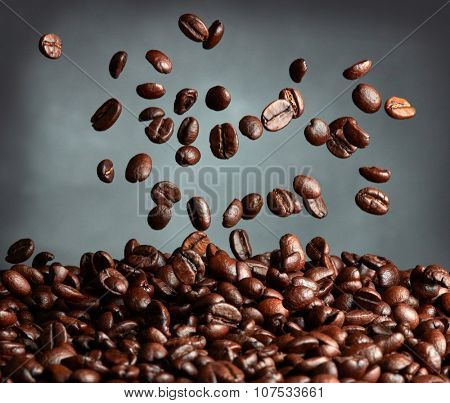Flying coffee beans over dark background