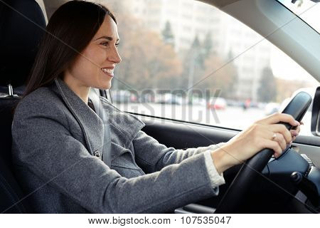 smiley woman in grey coat driving a car