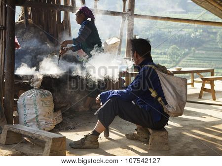 Asian minority man smoking beside a kitchen with a woman cooking