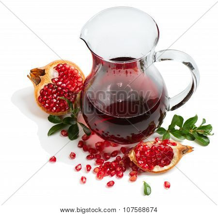 Freshly squeezed pomegranate juice in a pitcher and fruits and twigs of pomegranate tree isolated on white background poster