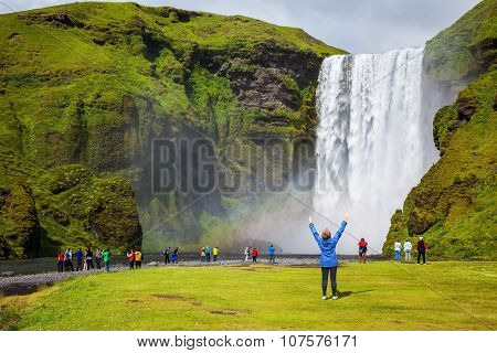Picturesque huge rainbow appears in the water mist. Middle-aged woman - tourist shocked beauty waterfall. Interesting waterfall in Iceland - Skogafoss
