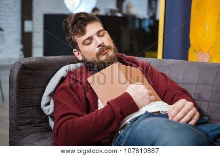 Bearded handsome tired man sleeping on grey sofa holding book