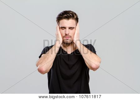 Young handsome attractive man closed his eyes and ears by hands