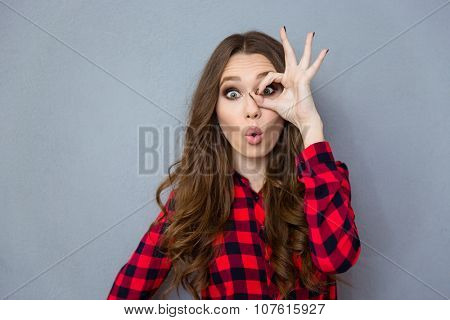 Funny amusing curly girl in checkered shirt showing okay gesture near her eye