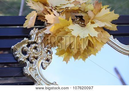 Wreath From Maple Leaves On A Mirror In Sky Reflexion
