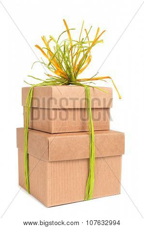 some brown cardboard gift boxes tied with natural raffia of different colors on a white background
