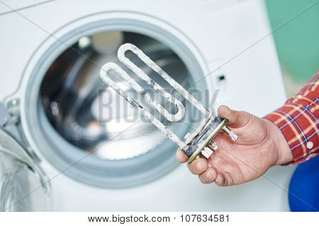 Washing machine repair. Hand of repairer with turbular electric heating element
