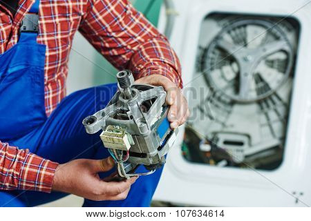 Washing machine repair. Repairer hands with electric engine motor in front of damaged unit