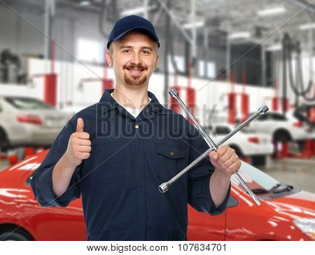 Smiling car mechanic with tire wrench over garage background.