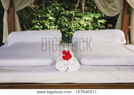 Spa bungalow, inner view. White bed and white towels with exotic flower