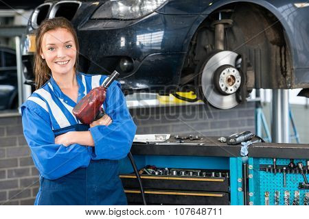 Portrait of happy female mechanic with pneumatic wrench standing by car in garage