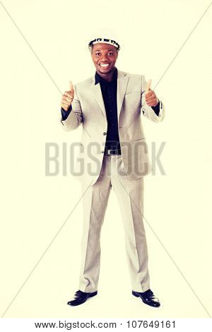 Happy successful businesman in helmet gesturinh thumbs up. Isolated on white.