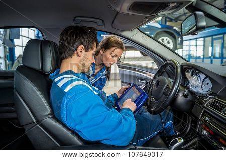 Female mechanic looking at male colleague using digital tablet in car at garage