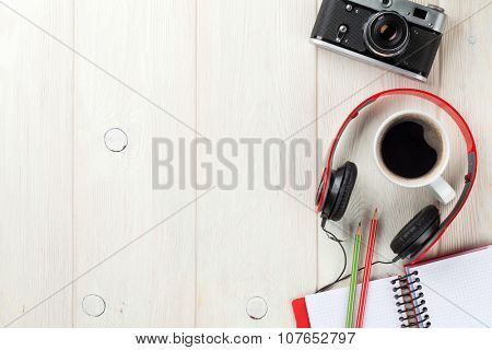 Set of travel stuff. Camera, headphones, notepad and coffee cup on wooden table. Top view with copy space poster