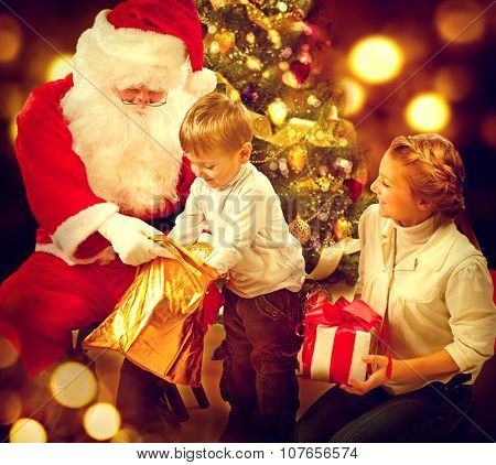 Santa Claus giving Christmas gifts to children. Santa and Happy Kids - Sister and Brother. Cute little Boy and Santa Claus holding Giftbox. Christmas Holiday Scene over Decorated Christmas Tree