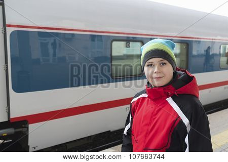 sad teenager boy standing near train