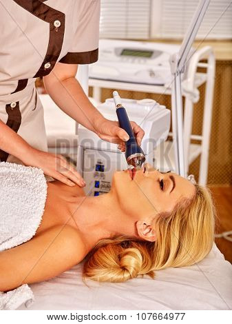 Young woman receiving electric ultrasonic facial massage at beauty salon. Hardware cosmetology. poster