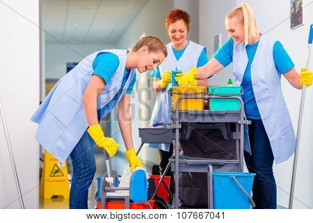 Commercial cleaning brigade working in corridor