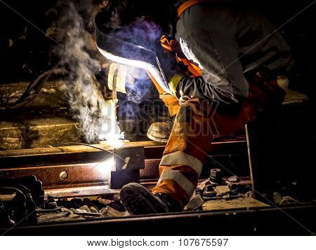 worker with protective mask and gloves welding train rail