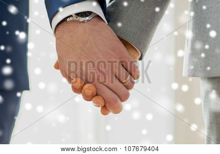 people, homosexuality, same-sex marriage and love concept - close up of happy male gay couple holding hands with wedding rings on over snow effect poster