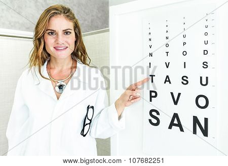 Female Oculist Doctor Pointing At Eye Sight Test Chart And Looking At Camera - Optic Medical Concept