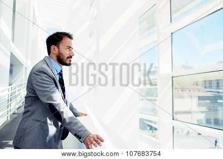 Thoughtful young male entrepreneur in suit resting after business meeting