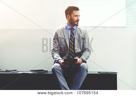 Young dreamy male managing director in luxury suit resting after work on his digital tablet