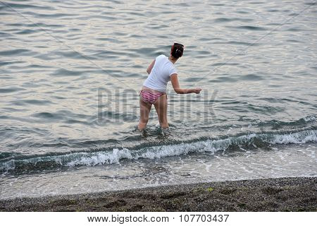 Woman Is Throwing Pebbles At The Beach Shallow.