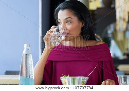 Closeup shot of young woman drinking a glass of water. African girl drinking water durinh her lunch break at restaurant. a Beautiful girl thirsty drink a glass of water and looking away.