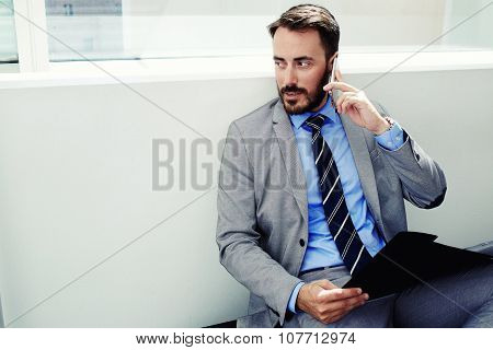 Handsome male manager in suit speaking on cell telephone during work break