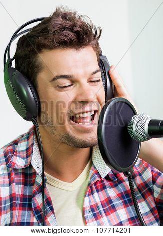 Closeup of male singer performing in recording studio poster