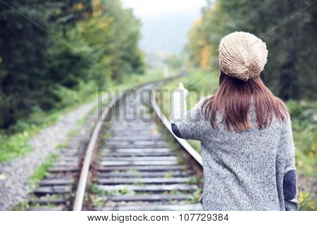 Young woman walking on rail of railway tracks