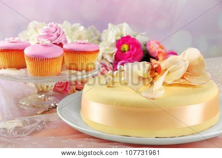 Cake with sugar paste flowers and cupcakes, on light background