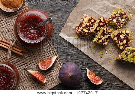 Glass jar with some fig jam and fig turkish delight with pistachio nuts on a dark wooden background. poster