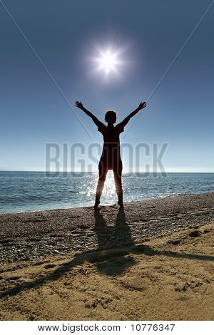 Woman silhouette stands on toes on sunny beach with hands up