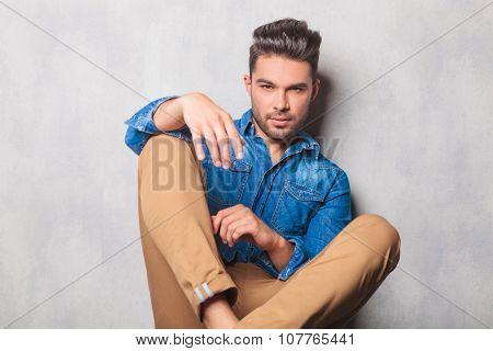 portrait of casual hansome man in denim shirt sitting in studio legs crossed