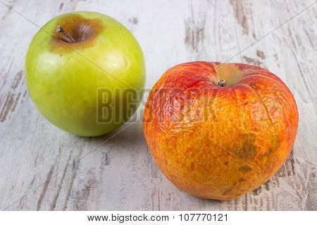 Spoiled Apple On Old Wooden White Table