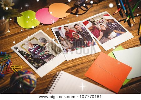 Snow against high angle view of office supplies with blank instant photos